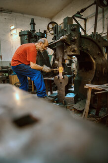 Senior blacksmith working in hammer mill - HHF005309