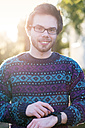 Portrait of smiling young hipster with smartwatch at backlight - BRF001183