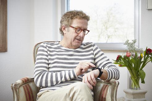 Senior man sitting in armchair using smartwatch - RHF000769