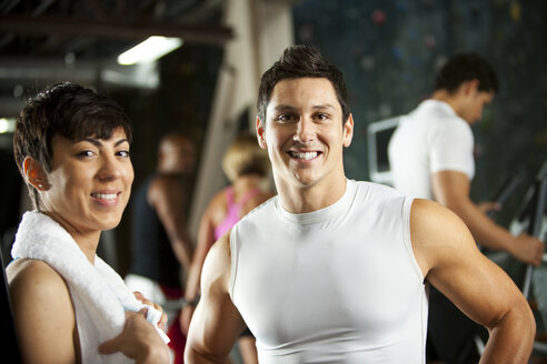 Portrait of smiling man and woman in a gym - SELF000056