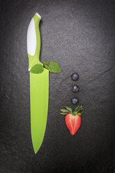 Bright green kitchen knife, sliced strawberry and three blueberries on slate - VTF000414