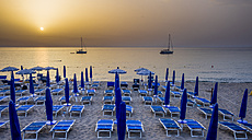 Italy, Sicily, Cefalu, view to beach umbrella and loungers in front of the sea at evening twilight - AMF003961