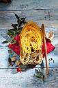 Two sorts of uncooked Tagliolini pasta, parmesan, chili pods, herbs, olive twig and cooking spoon - CSF025302