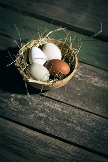 Easter nest with eggs in bowl on dark wood - MAEF010242
