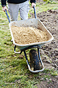 Man transporting sand in a wheelbarrow - HAW000788