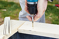Gardener screwing on wooden plank to build a raised bed - HAW000776