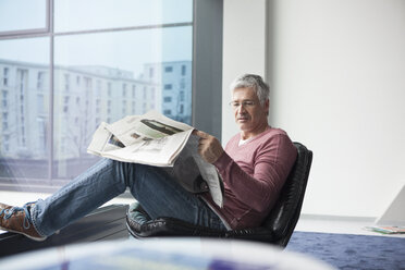 Man sitting in a leather chair reading newspaper - RBF002613