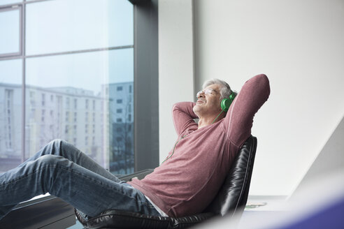 Man sitting in a leather chair hearing music with headphones - RBF002619