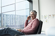 Man sitting in a leather chair telephoning with smartphone - RBF002631