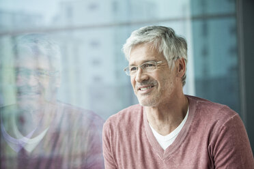 Portrait of smiling man looking through window - RBF002634