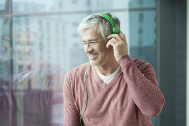 Man with green headphones looking through window - RBF002637
