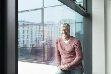 Portrait of smiling man with grey hair in front of a window - RBF002640