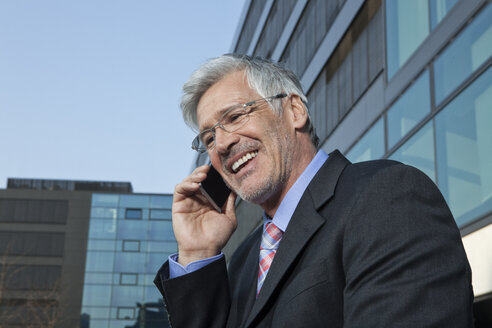 Portrait of smiling businessman telephoning with smartphone - RBF002643