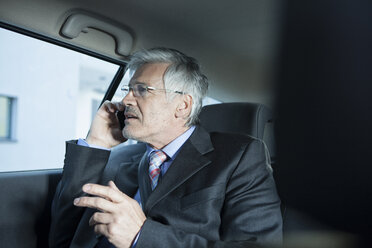 Businessman telephoning in a car - RBF002646