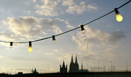 Germany, Colgone, Atmospheric sunset with light bulbs and cathedral - ONF000826