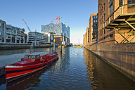 Germany, Hamburg, view to Elbe Philharmonic Hall under construction with moored red boat in the foreground - RJF000424