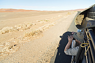 Namibia, Namib Desert, Namib Naukluft Park, Sossusvlei, man in a car looking through binoculars - CLPF000096