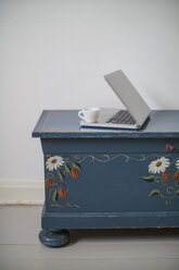 Coffee cup and laptop standing on old wooden chest - RIBF000007