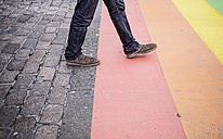 Netherlands, Maastricht, man walking on rainbow flag painted on the street - RIBF000033