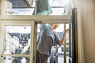 Germany, woman cleaning window at home - RIBF000027