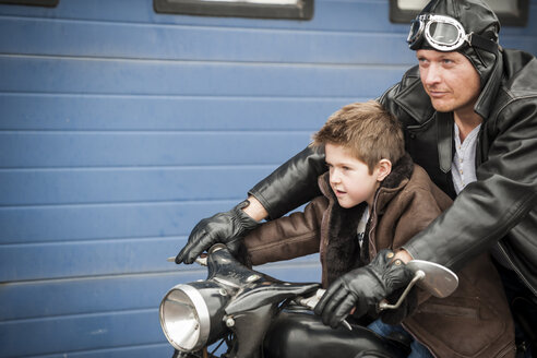 Father and son driving with vintage moped - PAF001281
