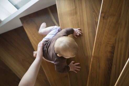 Mother's hand helping baby girl climbing up a stair - JTLF000105