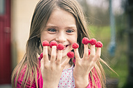 Happy girl with raspberries on her fingers - SARF001715