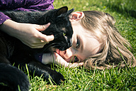 Girl lying on a meadow with black cat - SARF001727