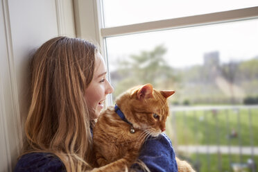Female teenager with cat looking through window - DISF002030