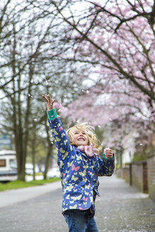 Little girl throwing cherry blossoms in the air - JFEF000626