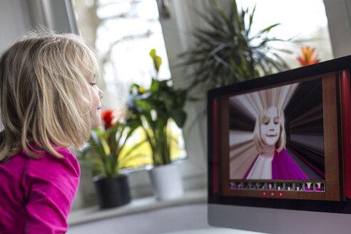 Little girl watching herself on flatscreen monitor - JFEF000621