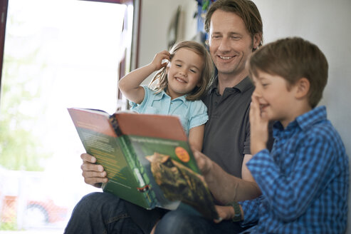 Father reading out book to his children - MAO000043