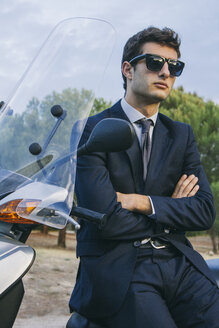 Portrait of young businessman wearimg sunglasses sitting on motor scooter - ABZF000007