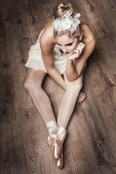 Female ballet dancer sitting on ground - DAWF000329