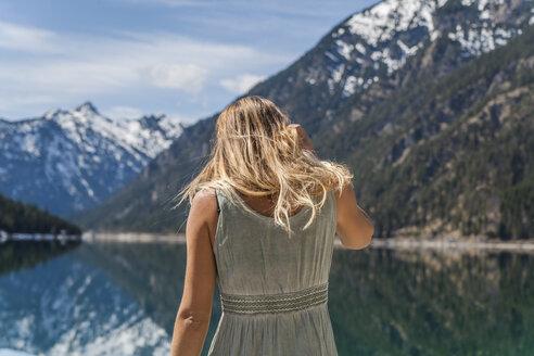 Austria, Tyrol, Lake Plansee, woman at lakeshore - TCF004621