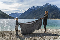 Austria, Tyrol, Lake Plansee, mother and daughter at lakeshore folding bath towel - TCF004604