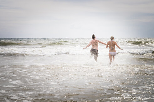 Mexico, Riviera Nayarit, young couple running into the sea - ABAF001666