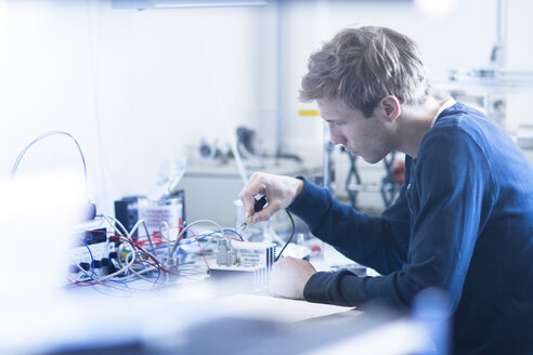 Technician constructing electric component part - SGF001524