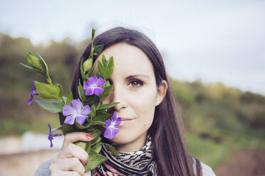 Woman in countryside holding bunch of periwinkles - GEMF000218