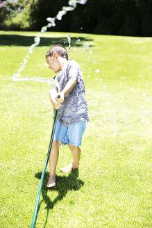 Boy splashing water with garden hose - TOYF000063