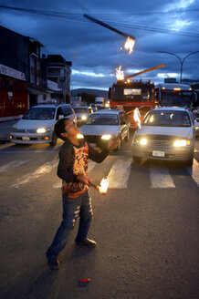 Bolivia, Cochabamba, street kid juggling with torches on street for donations - FLK000580