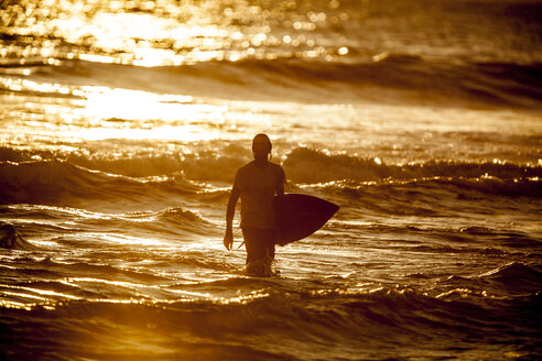 Indonesia, Bali, man with surfboard at twilight - KNTF000016