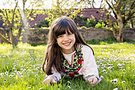 Portrait of smiling girl lying on a meadow - LVF003230