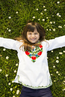Portrait of smiling girl lying on a meadow with outstretched arms - LVF003232