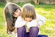 Two sisters sitting together on a meadow in the garden - LVF003235