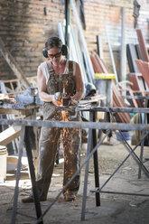 Female welder working in metal workshop - ABAF001673