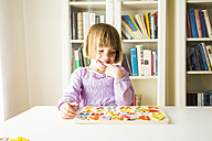 Portrait of smiling little girl learning alphabet with wooden letters - LVF003297