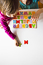 Two sisters with with wooden alphabet puzzle - LVF003286
