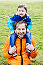 Happy father with son on his shoulders in a park - GEMF000224