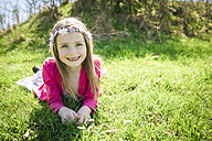 Portrait of smiling girl wearing flowers lying on a meadow - SARF001747